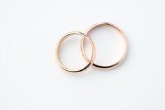 Dos anillos de bodas de oro aislados en blanco Imagen de archivo libre de regalías