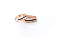 Dos anillos de bodas de oro aislados en blanco Fotografía de archivo