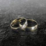 Dos anillos de bodas de oro en la superficie de piedra Imagen de archivo libre de regalías