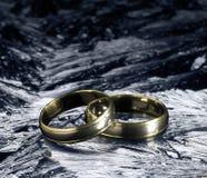 Dos anillos de bodas de oro en superficie del hielo Imagenes de archivo