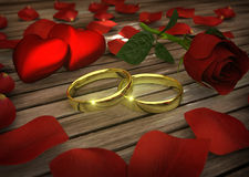 Dos anillos de bodas de oro y rosas del rojo con los pétalos Foto de archivo