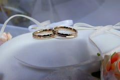 Dos anillos de bodas del oro blanco en el cojín blanco del cordón Fotografía de archivo libre de regalías