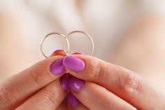 Dos anillos de bodas del oro en el brazo Pequeña profundidad del campo Foto de archivo