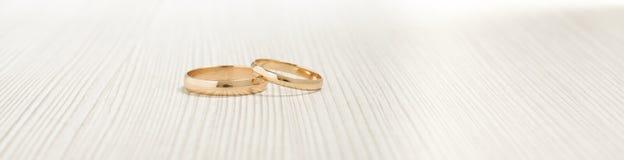 Dos anillos de bodas del oro en el fondo brillante Imágenes de archivo libres de regalías