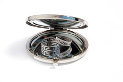 Dos anillos de bodas del oro en un pequeño espejo de cristal redondo Imagen de archivo