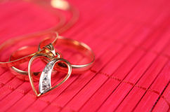 Dos anillos de bodas del oro y corazones del oro Foto de archivo libre de regalías