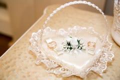 Dos anillos de bodas en el corazón blanco Imagen de archivo libre de regalías