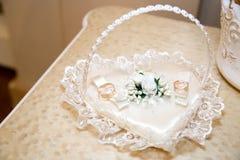 Dos anillos de bodas en el corazón blanco Foto de archivo