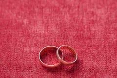 Dos anillos de bodas en el fondo del terciopelo rojo Imagen de archivo
