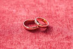 Dos anillos de bodas en el fondo del terciopelo rojo Imagenes de archivo