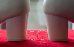 Dos anillos de bodas en el fondo del terciopelo rojo Zapatos blancos próximos de la boda Fotos de archivo