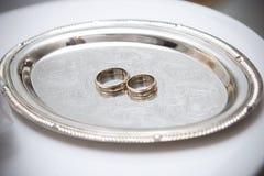 Dos anillos de bodas en la placa fotos de archivo libres de regalías