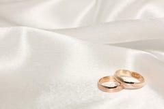 Dos anillos de bodas en la tela blanca Fotografía de archivo libre de regalías