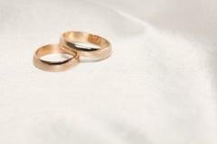 Dos anillos de bodas en la tela blanca Imagen de archivo libre de regalías