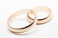 Dos anillos de bodas en la tela blanca Fotografía de archivo