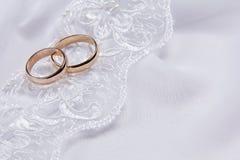 Dos anillos de bodas en la tela blanca Fotos de archivo