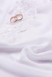 Dos anillos de bodas en la tela blanca Imagenes de archivo