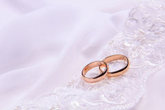 Dos anillos de bodas en la tela blanca Imágenes de archivo libres de regalías