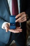 Dos anillos de bodas en las manos de un portador de anillo Imágenes de archivo libres de regalías