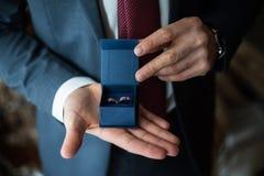 Dos anillos de bodas en las manos de un portador de anillo Fotos de archivo libres de regalías