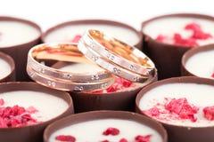 Dos anillos de bodas en los chocolates con las frambuesas Foto de archivo libre de regalías