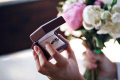 Dos anillos de bodas en muestra del infinito Concepto del amor la boda de dos gemelos de las hermanas sostener una caja Foto de archivo libre de regalías