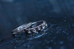 Dos anillos de bodas en un fondo azul Imagen de archivo