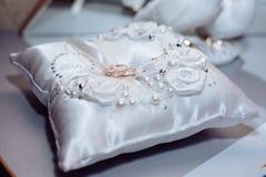 Dos anillos de bodas en un fondo de la tela Imagen de archivo