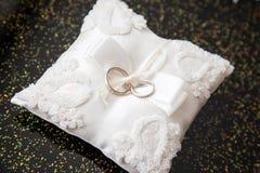 Dos anillos de bodas en una almohada Fotos de archivo