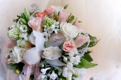 Dos anillos de bodas están entre las flores fotos de archivo libres de regalías
