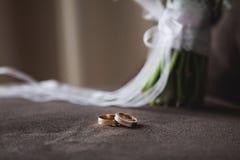 Dos anillos de bodas mienten en una butaca en el fondo un ramo de la boda Imagen de archivo
