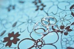 Dos anillos de bodas de oro blanco en una caja azul del metal imágenes de archivo libres de regalías