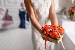 Dos anillos de bodas de oro que ponen en la bandeja de rosas anaranjadas en las manos de mujeres accesorios para la novia y el no Fotografía de archivo