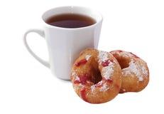 Dos anillos de espuma con el atasco y una taza de té Imagen de archivo libre de regalías