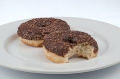 Dos anillos de espuma esmaltados chocolate del anillo con uno mordidos servido en un whi Imagenes de archivo