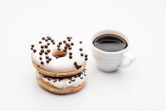dos anillos de espuma y tazas de café en el fondo blanco Imagen de archivo