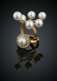 Dos anillos de la joyería con las perlas en fondo negro con reflectio Imagenes de archivo