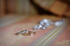 Dos anillos de oro en la alfombra en día de boda Fotografía de archivo libre de regalías