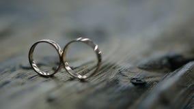 Dos anillos de oro en sesión fotográfica en la tabla de madera al aire libre en la boda almacen de video