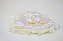 Dos anillos de oro que se casan en un amortiguador Foto de archivo libre de regalías