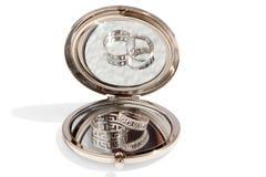 Dos anillos de oro que se casan en un pequeño espejo de cristal redondo Foto de archivo