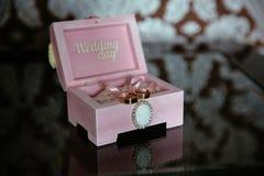 Dos anillos en una caja con la inscripción del día de boda en la tabla oscura Concepto de boda Fotografía de archivo libre de regalías