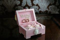 Dos anillos en una caja con la inscripción del día de boda en la tabla oscura Concepto de boda Fotografía de archivo