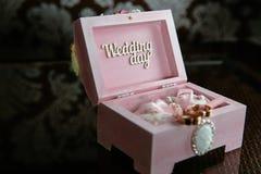 Dos anillos en una caja con la inscripción del día de boda en la tabla oscura Concepto de boda Foto de archivo libre de regalías