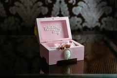 Dos anillos en una caja con la inscripción del día de boda en la tabla oscura Concepto de boda Imagen de archivo libre de regalías