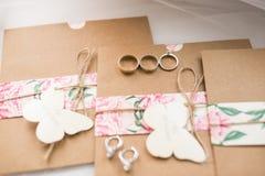 Dos anillos y anillos de compromiso de oro que mienten en las invitaciones de la boda en los sobres del arte Concepto de la boda  Fotografía de archivo
