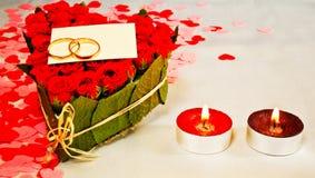 Dos anillos y una tarjeta en blanco con dos velas Imagen de archivo libre de regalías