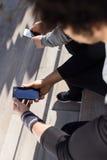 Dos aptos y hombres deportivos del youn que usan el teléfono móvil en la ciudad Imágenes de archivo libres de regalías