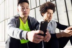 Dos aptos y hombres deportivos del youn que usan el teléfono móvil en la ciudad Fotografía de archivo libre de regalías
