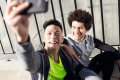 Dos aptos y hombres deportivos del youn que usan el teléfono móvil en la ciudad Fotografía de archivo